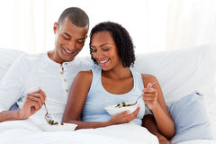 Loving couple having breakfast lying on their bed Royalty Free Stock Image