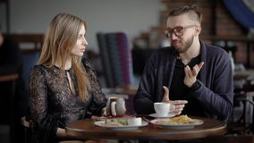 Loving couple having date in cafeteria. Happy man and woman sitting at the served table with food and beverages spending. Loving couple is having date in stock footage