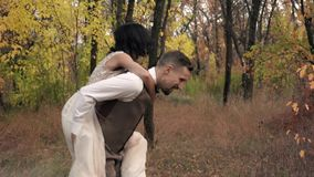 A woman in a white dress jumps on the back of a man in a suit and laughs, a walk in an autumn park, slow motion. A loving couple having fun and laughing in an stock video