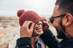 Loving couple having fun outdoors. Man covering eyes of women with cap Royalty Free Stock Photos