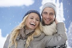 Loving couple having fun in snowfall Royalty Free Stock Photography