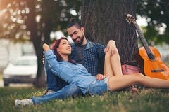 Loving couple holding each other sitting on a tree trunk o. N a romantic date in the park forest Royalty Free Stock Images