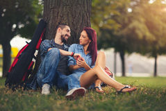 Loving couple holding each other sitting on a tree trunk. On a romantic date in the park forest Royalty Free Stock Photography
