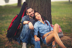 Loving couple holding each other sitting on a tree trunk. On a romantic date in the park forest Stock Images