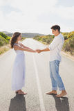Loving couple holding hands on countryside road Royalty Free Stock Photos