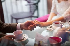 Loving couple holding hands, drinking tea in a cafe at the glass table. Breakfast or lunch at the restaurant. Engagement, royalty free stock photo