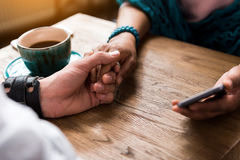 Loving couple holding hands with gentleness. Close up of man and woman bonding arms together. Cup of coffee on wooden table Royalty Free Stock Photo