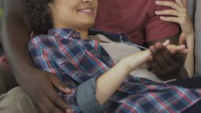 Loving couple holding hands and hugging on sofa home, family planning, rest time stock video