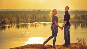 Loving couple holding hands on the river. Stock Images