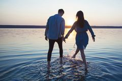 A loving couple holding hands is on the water. royalty free stock photo