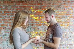 The loving couple holds the burning candle in hand. The woman is pregnant. Royalty Free Stock Image