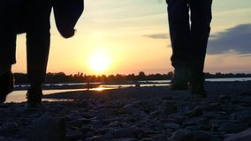 A loving couple holds hands and runs along a stony bank in the background of a sunset. HD, 1920x1080. slow motion. A loving couple holds hands and runs along a stock footage