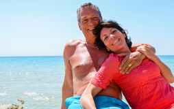 Loving couple on holiday at the beach by the transparent turquoise Royalty Free Stock Photos