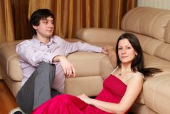 Loving couple at home. Young man and woman sitting at a distance Stock Images