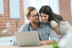 Loving couple at home websurfing on laptop Royalty Free Stock Photography