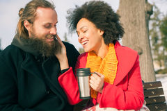 Loving couple with hot drinks sitting on bench in winter Royalty Free Stock Images
