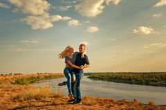 Loving couple hugging on bank of river. Stock Images