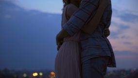 Loving couple hugging each other and whispering tenderness on roof at dusk stock video footage