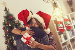 Exchanging Christmas presents. Loving couple hugging and exchanging presents on a Christmas morning Stock Photography