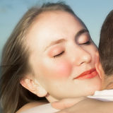 Loving couple hugging with focus on woman's face. Young beautiful blond woman giving her partner a hug with loving expression on her face and a soft smile Royalty Free Stock Images