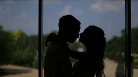 Loving couple hugging and kissing in the dark. Silhouette of loving couple in embrace in the background of a big window and kisses. Loving couple hugging and stock video footage