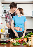 Loving couple hugging in  kitchen. Young loving couple hugging in home kitchen Royalty Free Stock Images