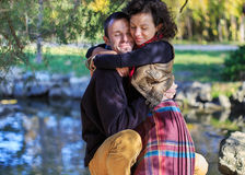 Loving couple hugging in the park. Loving couple in bright clothes hugging each other in the park near the lake Royalty Free Stock Image