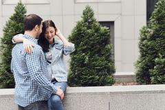 Loving couple hugging sitting on parapet. royalty free stock image