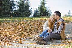 Loving couple hugging while sitting on steps in park during autumn Royalty Free Stock Images