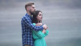 Loving couple is hugging by standing near lake shore Smooth motion frame. Man in plaid shirt and a woman in azure evening dress stock video footage