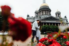 Loving couple hugs against a background of red flowers and vintage architecture. Walk on St. Valentine Day kiss Stock Image