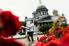 Loving couple hugs against a background of red flowers and vintage architecture. Walk on St. Valentine Day kiss. Picked up the arms. Fun and fooling around Royalty Free Stock Photos