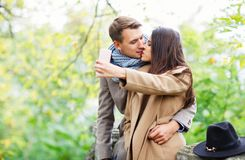 A loving couple kiss and do selfie on a mobile phone. Outside in the park, Stock Photo