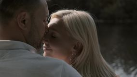 Loving couple kiss sitting on a pier near the river. Close-up. Slow motion stock video