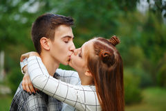 Loving couple kiss teens. Loving couple teens kiss passionately. Girlfriend and boyfriend together. Close-up. First love. He falls in love. Date. First kiss Royalty Free Stock Photography