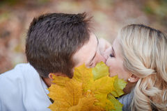 Loving couple kissing in autumn park Stock Photos