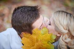Loving couple kissing in autumn park Stock Photos
