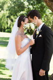Loving couple kissing behind bouquet in garden Stock Photography