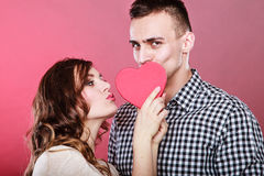 Loving couple kissing behind red heart. Love. Stock Images