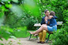Loving couple kissing on a bench Stock Photos