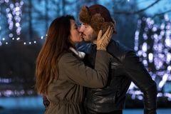 Loving couple kissing on a date in at ice rink Royalty Free Stock Photography