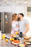 Loving Couple Kissing in Kitchen royalty free stock image