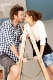 Loving couple kissing on ladder. In house under construction Royalty Free Stock Images