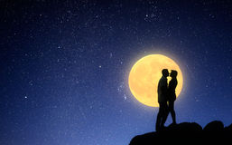 Loving couple kissing on a moonlit night. Light of the full moon night. Silhouette of a loving couple on a background of the sky. Kiss on a romantic date Stock Photography
