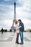 Loving couple kissing near the Eiffel Tower in Paris. Lovers kissing in Paris with the Eiffel Tower in the Background Royalty Free Stock Image