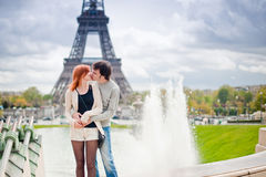 Loving couple kissing near the Eiffel Tower in Paris. Lovers kissing in Paris with the Eiffel Tower in the Background Stock Images