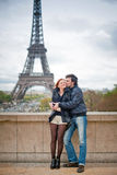 Loving couple kissing near the Eiffel Tower in Paris. Lovers kissing in Paris with the Eiffel Tower in the Background Royalty Free Stock Photos