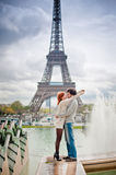 Loving couple kissing near the Eiffel Tower in Paris. Lovers kissing in Paris with the Eiffel Tower in the Background Royalty Free Stock Images