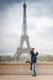 Loving couple kissing near the Eiffel Tower in Paris. Lovers kissing in Paris with the Eiffel Tower in the Background Stock Image
