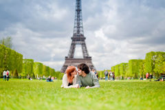 Loving couple kissing near the Eiffel Tower in Paris. Loving couple lying on the grass on the Champ de Mars in Paris with the Eiffel Tower in the Background Stock Image